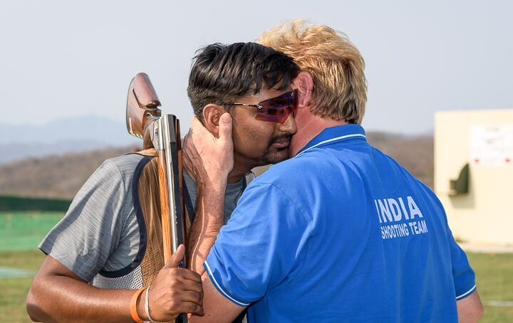 Ankur Mittal congratulated by coach Marcello Dradi. Photo - ISSF